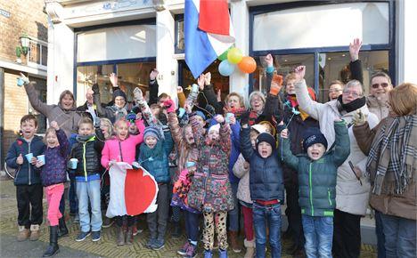 Officiele heropening Wereldwinkel Harlingen met juichende mensen voor winkel